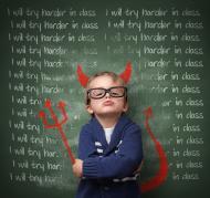 Naughty school boy erasing I'll try harder on a blackboard