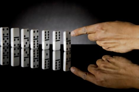 hand pushing the first domino in a line